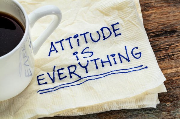 attitude is everything - motivational slogan on a napkin with a cup of coffee